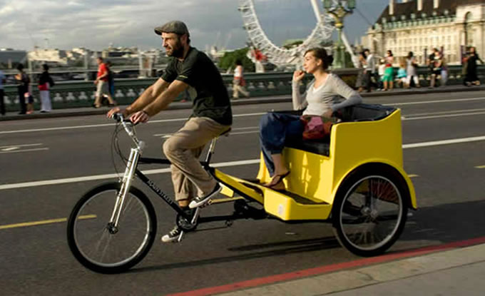 A pedicab in london with the london eye in the background